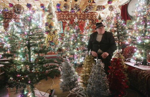 mecys vaitkevicius sits in his home decorated for christmas with 100 plastic christmas trees and 35,000 electric light bulbs, in the village of simaniskes, some 100 km (62 miles) east of the lithuanian capital, vilnius, thursday, dec. 23, 2004. vaitkevicius, a retired engineer, has made it a holiday habit to turn his modest house into a shrine of lights for himself and his friends. (ap photo/mindaugas kulbis)  publicerad text: lyser upp lettland.